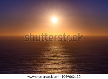 Beautiful colorful sunset into the atlantic sea in Africa. Amazing colors of starburst sun above the horizon about to set into the ocean