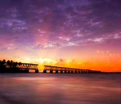 Beautiful colorful sunset or sunrise with broken bridge and sun rays spreading through purple clouds. Taken at Bahia Honda state park in the Florida Keys, near famous tourist destination of Key West.
