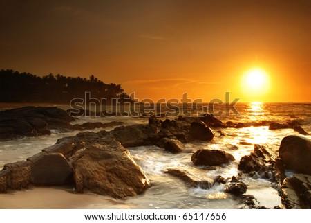 Beautiful colorful sunset over sea and boulders on Sri Lanka