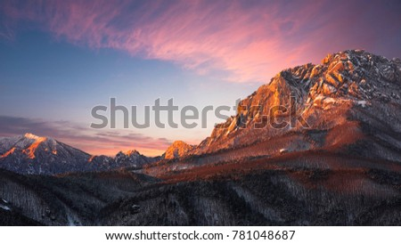 Beautiful colorful sunset over Seoraksan National Park in winter. Mountains with pine trees and rocky cliffs. The light was struck. Snow-covered #781048687