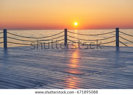 Beautiful colorful sunset over the sea and the sun shines. Orange sky #671895088