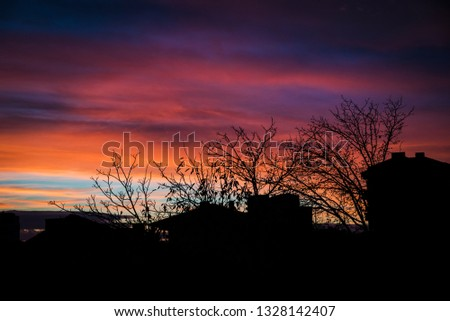 Beautiful colorful sunset sky - purple and orange clouds and houses silhoettes #1328142407