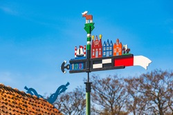 Beautiful colorful weathercock waving in the Curonian Spit in Nida fishermen's village, Lithuania, Europe with blue sky and roof with heads of horses on background