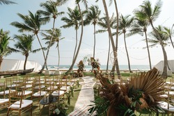 Beautiful colorful wedding planner setup. Wedding arch with natural flowers outdoors, beautiful palm trees and beach as background