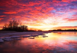 Beautiful colorful winter landscape with frozen lake and sunset sky. Unusual weather phenomenon