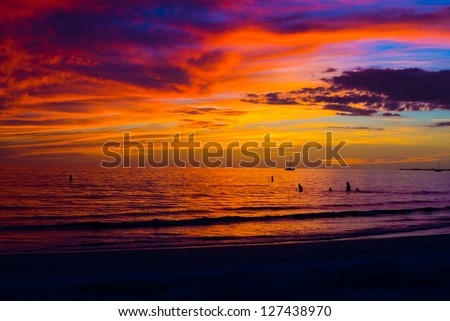 Beautiful colors of a winter sunset over the water of the Gulf of Mexico at Ft Myers Beach in Florida, placing the sailboat and swimmers in silhouette. - stock photo