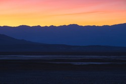 Beautiful, colourful and vibrant golden desert sunset or sunrise with mountain ridge silhouette in the rugged landscape of Death Valley National Park, USA.