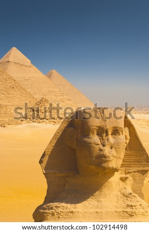 Beautiful composite of all the Giza pyramids behind a close-up of the head of the Great Sphinx on a clear sunny, blue sky day in Cairo, Egypt. Vertical copy space