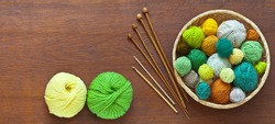 Beautiful composition with accessories for hand knitting: balls of colorful yarn in basket, knitting needles and crochet hooks on wooden background. Needlework and hobby. DIY concept. Flat lay, mockup