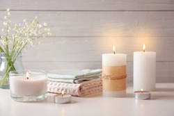 Beautiful composition with burning wax candles on table