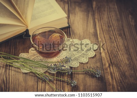 beautiful composition with cup of tea and book with flower. reading book time. cozy tea party with book. soft focus. #1103515907