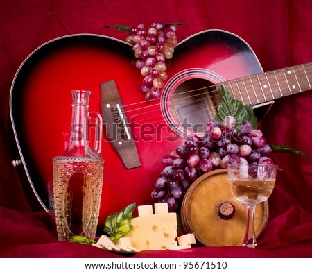 Beautiful composition with wine, grape, cheese and guitar on red background