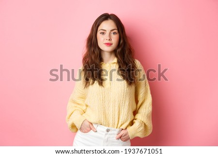 Beautiful confident girl with glamour hairdo, holding hands in pockets, smiling and looking self-assured, express confidence, standing against pink background Foto stock ©