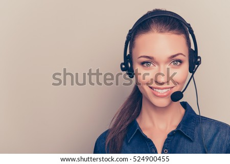 Beautiful consultant of call center in headphones on gray background. #524900455
