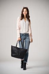 Beautiful cool woman holding black shopping bag and walking on grey background. Fashion girl wearing pink cardigan, jeans and polka dot shirt. Stylish casual woman holding a big bag and looking away.