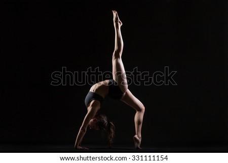 Beautiful cool young fit woman in sportswear doing sport exercise, backbend, One-legged Upward Bow (Wheel) Posture, Eka Pada Urdhva Dhanurasana, full length, side view, studio shot, black background