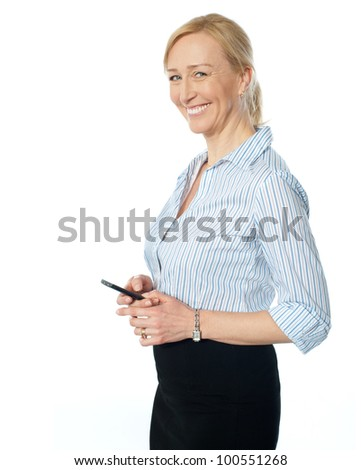 Beautiful corporate female using cellphone, smiling and looking at camera