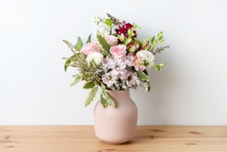 Beautiful cottage style flower arrangement, in a pink vase, on a wooden table. Flower bunch includes Roses, Snapdragons, Ranunculus, Daisy's, Chrysco, Lily of the Incas, Thryp and lush green foliage.