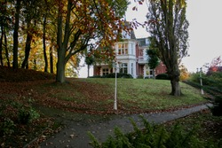 Beautiful country house with yellowed trees, walking path and stairs on a Sunny autumn day at sunset. Golden hour. City life.