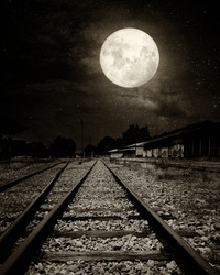 Beautiful countryside Railroad with Milky Way star in night skies, full moon - Retro style artwork with vintage color tone (Black and white vintage film grain filter effect styles)