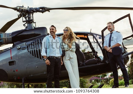 Beautiful couple alighted from a private helicopter and looking at a view with pilot standing by. Couple standing by a private aircraft with pilot.