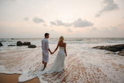 beautiful couple at sunset near the ocean.Honeymoon romantic couple in love holding hands walking on beautiful sunset at beach. Lovers or newlywed married young couple by the sea. Wedding in Thailand