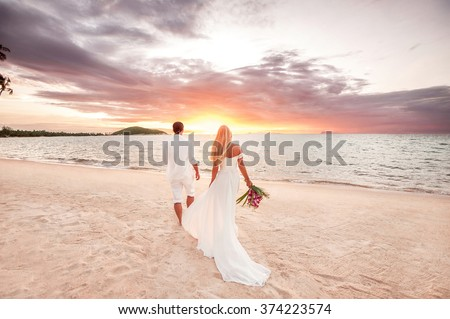 beautiful couple at sunset near the ocean.Honeymoon romantic couple in love holding hands walking on beautiful sunset at beach. Lovers or newlywed married young couple by the sea. Wedding in Thailand. Stockfoto ©