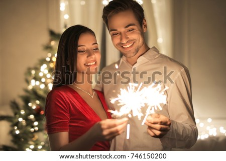 Beautiful couple celebrating New Year's Eve with spark and shiny fireworks #746150200