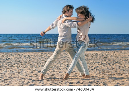 beautiful couple dancing on the beach at the background of the sea