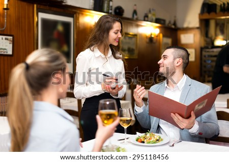 Beautiful couple dining in a restaurant while happy waitress is taking their order