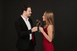 Beautiful couple drinking champagne on grey background. Man wearing suit and woman wearing red dress celebrating Valentine`s day