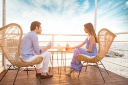 Beautiful couple drinking cocktail in the sunset