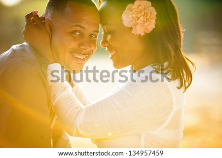 Beautiful couple embracing and caught in a rainbow of sunshine