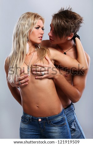 Beautiful couple embracing and fashion posing in studio