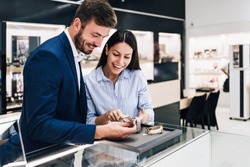 Beautiful couple enjoying in shopping at modern jewelry store. Close up shot of human hand holding expensive watch.