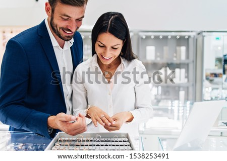 Beautiful couple enjoying in shopping at modern jewelry store. Close up shot of woman's hand with gorgeous expensive ring and bracelet.