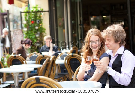Beautiful couple having a date in a cafe and drinking pink wine