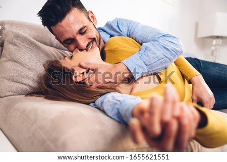 Beautiful couple having a romantic kiss lying on the sofa in the living room at home.