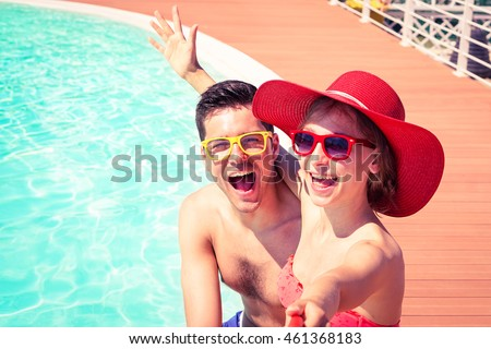 Beautiful couple having fun taking selfie at swimming pool  - Cheerful friends enjoy mobile photo camera using stick on sunny day  - Concept of happy moments on board of touristic ship - Focus on male