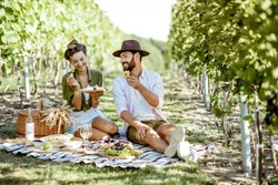 Beautiful couple having romantic breakfast with lots of tasty food and wine, sitting together on the picnic blanket at the vineyard on a sunny morning