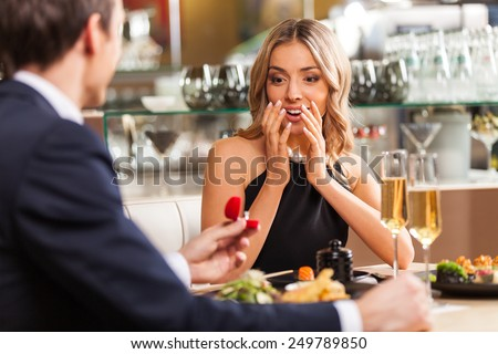 Beautiful couple having romantic dinner at restaurant back view of man proposing to woman in restaurant