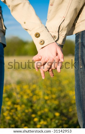 Beautiful couple holding hands on the field