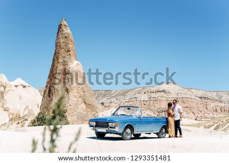 beautiful couple hugging near a blue cabriolet, sharp peaks of mountains in the background