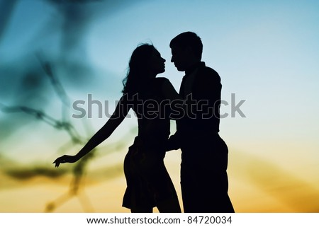 Beautiful couple in love at sunset. Silhouette guys and girls at sunset. They dance.