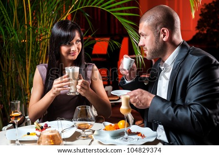 Beautiful couple in love drinking coffee at restaurant