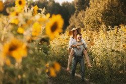 Beautiful couple in love is embracing, looking at the sunset over a field of sunflowers. Girl in a hat and white summer dress, a man in jeans and a tshirt. Summer vacation concept, recreation in the