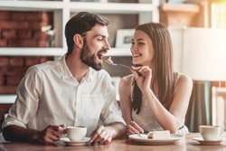 Beautiful couple in love is sitting in cafe, drinking coffee and eating cheesecake. Young woman is feeding her man. Looking softly on each other.