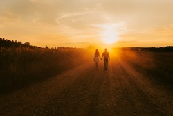 Beautiful couple in love is walking the road between the fields of sunflowers, summer sunset, bright orange light. In the background is a forest and rustic wooden houses. Concept of travel by car, eco