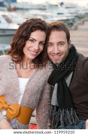 Beautiful couple in love sitting on wooden pier in marina