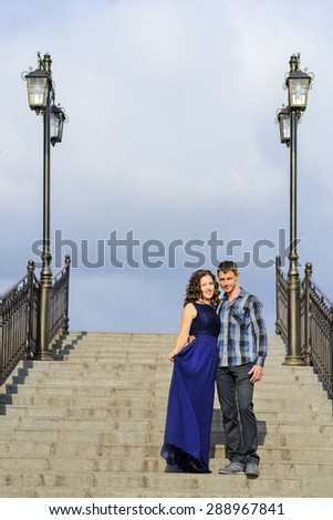 Beautiful couple in love standing on stone stairs with lanterns